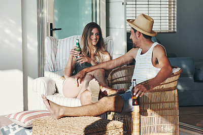 Buy stock photo Full length shot of an affectionate young couple drinking beers while relaxing on the patio