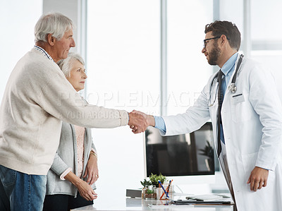 Buy stock photo Cropped shot of a confident young male doctor shaking a senior patient's hand after a consultation