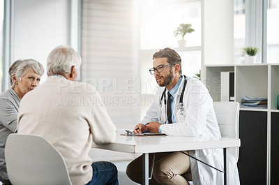 Buy stock photo Cropped shot of a confident young male doctor consulting a mature patient inside of the doctor's office