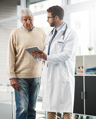 Buy stock photo Cropped shot of a young male doctor showing his senior male patient something on a digital tablet