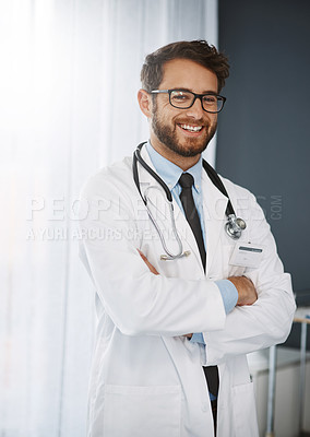 Buy stock photo Cropped portrait of a confident young male doctor standing with his arms folded inside of a hospital