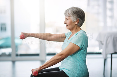 Buy stock photo Cropped shot of a healthy senior woman working out with dumbbells