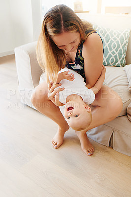 Buy stock photo Shot of a young woman and her adorable baby girl playing together on the sofa at home