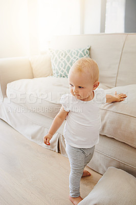 Buy stock photo Shot of an adorable baby girl learning to walk at home