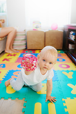 Buy stock photo Portrait of an adorable baby girl playing with a toy at home