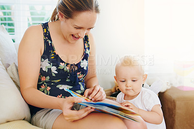 Buy stock photo Shot of an adorable baby girl reading a book together with her mother at home