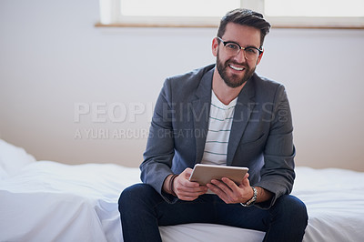 Buy stock photo Cropped portrait of a handsome young businessman working on a tablet while sitting on his bed at home
