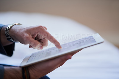 Buy stock photo Cropped shot of an unrecognizable businessman working on a tablet while sitting on his bed at home