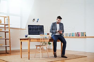 Buy stock photo Cropped shot of a handsome young businessman working on a tablet while sitting in his home office