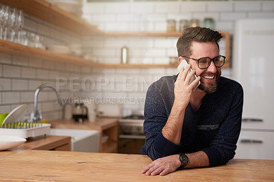 Buy stock photo Cropped shot of a handsome young man making a phonecall while standing in the kitchen at home