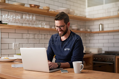 Buy stock photo Cropped shot of a handsome young businessman working on his laptop while sitting in the kitchen at home