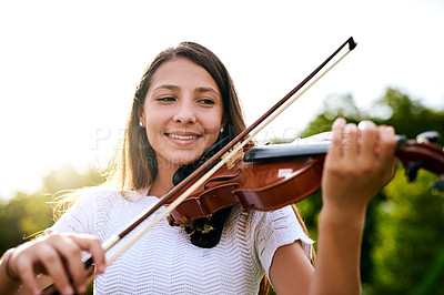 Buy stock photo Shot of a cheerful young girl playing the violin while standing in the backyard of her home during the day