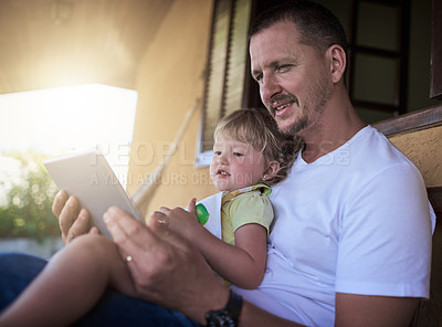 Buy stock photo Shot of a father and his little daughter using a digital tablet together outdoors
