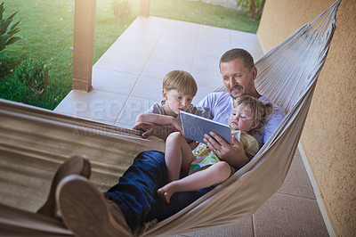 Buy stock photo Shot of a father and his two little children using a digital tablet while relaxing on a hammock outdoors