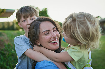 Buy stock photo Shot of a mother bonding with her two little children outdoors