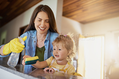 Buy stock photo Shot of a mother and her little daughter doing chores together at home