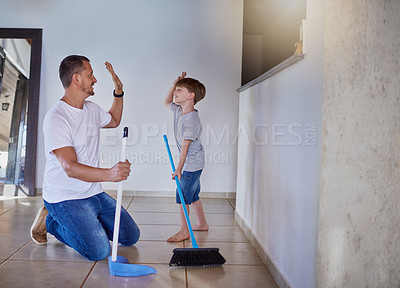 Buy stock photo Shot of a father and his little son high fiving each other while sweeping the floor at home