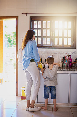 Buy stock photo Rearview shot of a mother and her little son washing dishes together at home