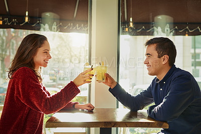 Buy stock photo Shot of a young man and woman toasting with their drinks on a romantic date at a coffee shop