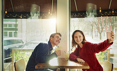 Buy stock photo Shot of a young man and woman taking selfies on a date at a coffee shop