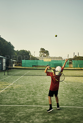 Buy stock photo Full length shot of a young boy working on his serve during tennis practice