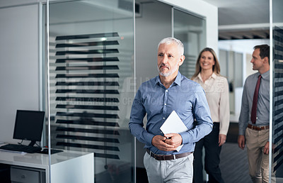Buy stock photo Shot of a mature businessman walking down a corridor in an office with his colleagues in the background