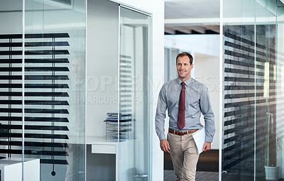 Buy stock photo Shot of a young businessman walking down a corridor in an office