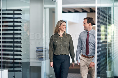 Buy stock photo Shot of two businesspeople walking down a corridor in an office
