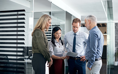 Buy stock photo Shot of a group of businesspeople going through paperwork in an office