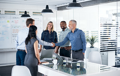 Buy stock photo Shot of a businessman and businesswoman shaking hands during a team meeting in a modern office