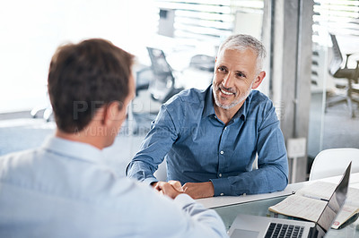 Buy stock photo Shot of two businessmen shaking hands during a meeting in a modern office