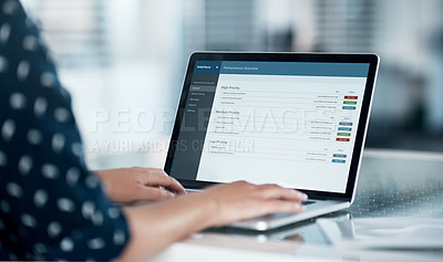 Buy stock photo Cropped shot of a businesswoman using a laptop at her desk in a modern office