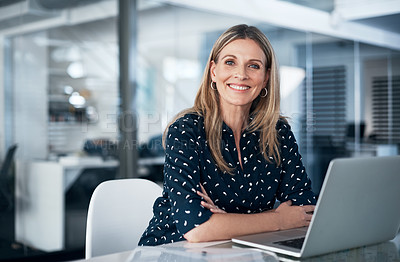 Buy stock photo Portrait of a mature businesswoman using a laptop at her desk in a modern office