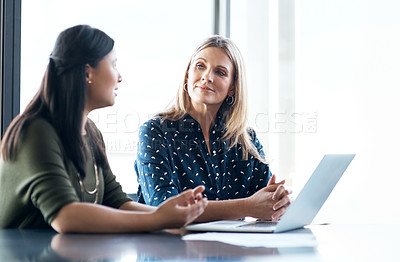 Buy stock photo Shot of two businesswomen  using a laptop together in a modern office