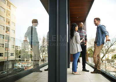 Buy stock photo Full length shot of three businesspeople meeting on the balcony of their office