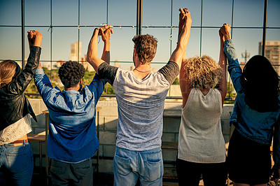Buy stock photo Rearview shot of unrecognizable friends spending the day outside on a rooftop
