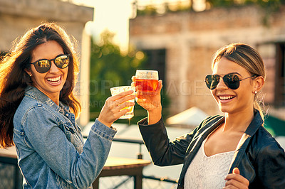 Buy stock photo Cropped shot of two female best friends spending the day outside on a rooftop
