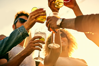 Buy stock photo Low angle shot of a group of young friends having a drink and spending the day outside on a rooftop