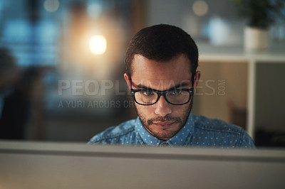 Buy stock photo Cropped shot of a young businessman working in a modern office at night