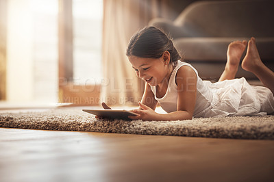 Buy stock photo Shot of an adorable little girl using a digital tablet on the floor at home