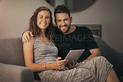 Buy stock photo Portrait of a young couple using a digital tablet together while relaxing on the sofa at home