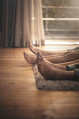 Buy stock photo Cropped shot of a family lying down together on the floor at home