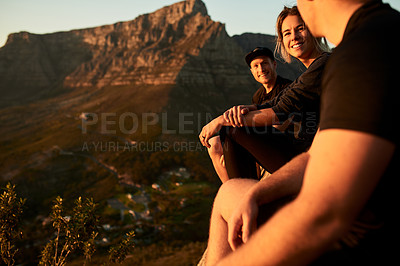 Buy stock photo Cropped shot of three young friends sitting down while taking a break from their mountain hike