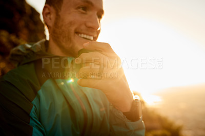 Buy stock photo Cropped shot of a young man taking a coffee break during his mountain hike