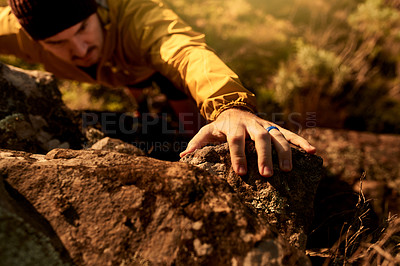 Buy stock photo Closeup shot of an unrecognizable young man's hand gripping a rock during a hike in the mountains