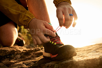 Buy stock photo Cropped shot of an unrecognizable young man tying his laces during a hike in the mountains