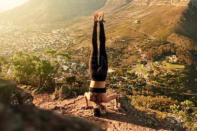 Buy stock photo Full length shot of an unrecognizable young woman doing a handstand while hiking in the mountains