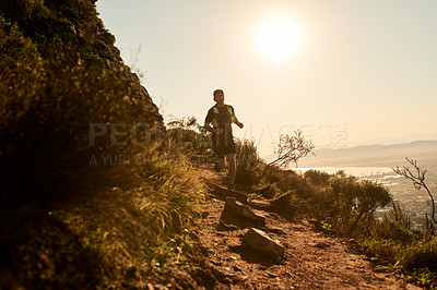 Buy stock photo Full length shot of a young man taking an early morning hike through the mountains