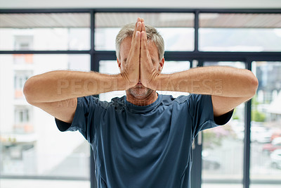 Buy stock photo Shot of an unrecognizable middle aged man doing yoga poses and holding his hands together in front of his face while standing inside of a studio
