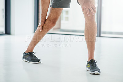 Buy stock photo Shot of an unrecognizable man holding his leg due to pain while  standing inside of a studio during the day